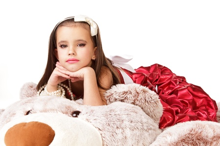 red evening: Beautiful little girl in red evening dress lying on big toy on white background