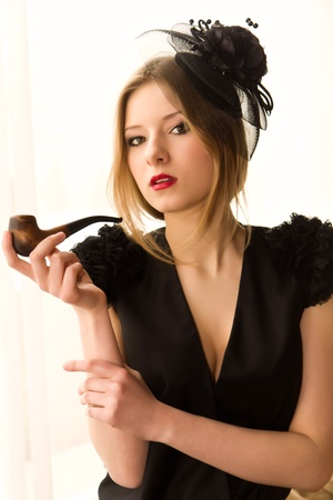 Retro woman portrait with smoking pipe in classic interior photo