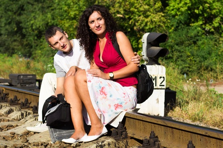 Beautiful happy love couple on rails waiting for train outdoor  photo