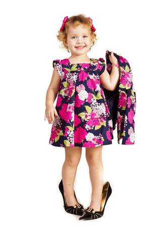 big girl: Beautiful little girl in high-heeled shoes over white background Stock Photo