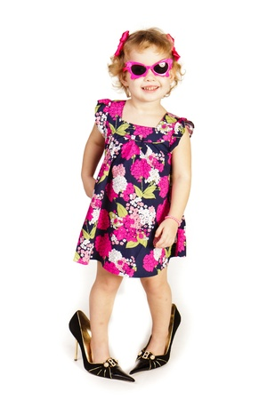 Beautiful little girl in high-heeled shoes over white background photo