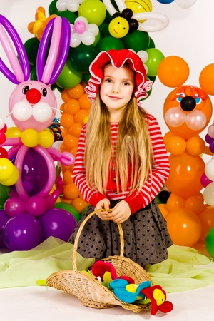 Beautiful little girl as red Riding Hood in balloon forest with balloon flower photo