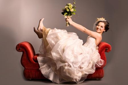 Portrét krásné šťastná nevěsta na červené pohovce ve studiu