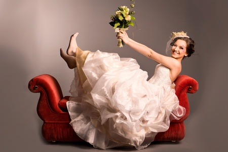 Portrait of a beautiful happy bride on red sofa in studio photo