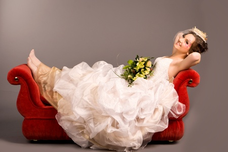 Portrait of a beautiful happy bride on red sofa in studio Stock Photo
