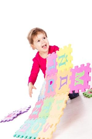 Roztomilá holčička řešení abeceda puzzle na bílém pozadí Reklamní fotografie