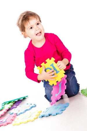 Little cute girl solving alphabet puzzle over white background Stock Photo - 13297607