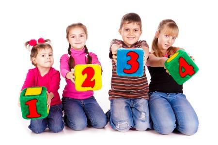 Des enfants heureux de maintien des blocs avec des chiffres sur fond blanc Banque d'images