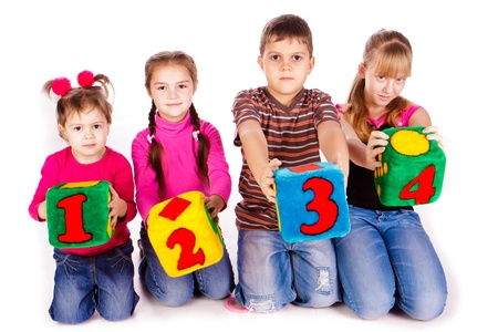 Happy kids holding blocks with numbers over white background Stock Photo - 13297706