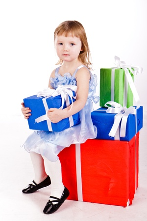 Little girl with gift boxes isolated on white photo