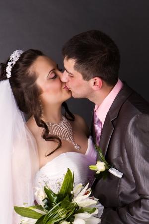 Happy bride and groom kissing in studio photo