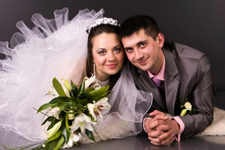 Happy bride and groom lying in studio photo