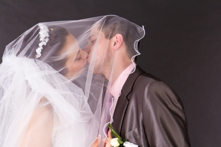 Happy bride and groom kissing under the veil in studio photo