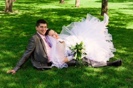 Happy bride and groom  lying on grass outdoor photo