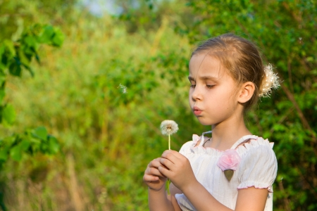 Beautiful girl with dandelion blowing  photo