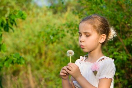 Beautiful girl with dandelion blowing  photo