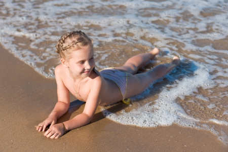 Little girl lying on the beach in water Stock Photo - 14319246
