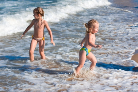 bathe: Little girls in the spray of waves at sea on a sunny day