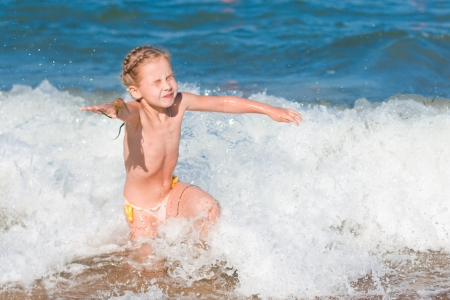 sun bathing: Little girl crying in the spray of waves at sea on a sunny day Stock Photo