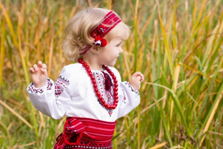 log basket: Beautiful girl in ukrainian costume sitting in a field outdoor Stock Photo
