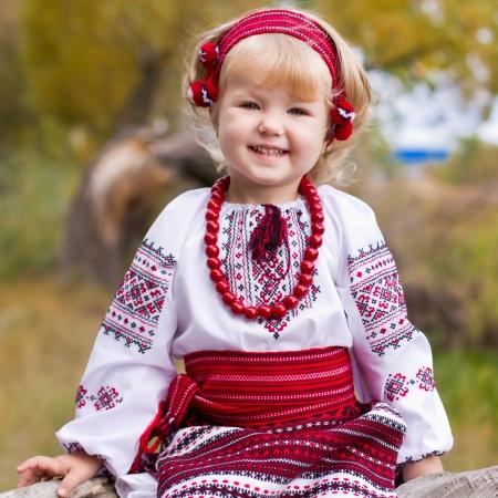 Krásná dívka v ukrajinském kroji sedí na log venkovní