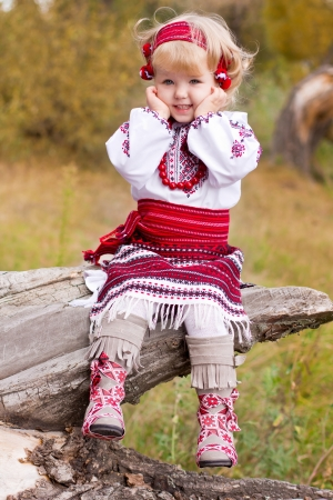 Beautiful girl in ukrainian costume sitting on a log outdoor photo