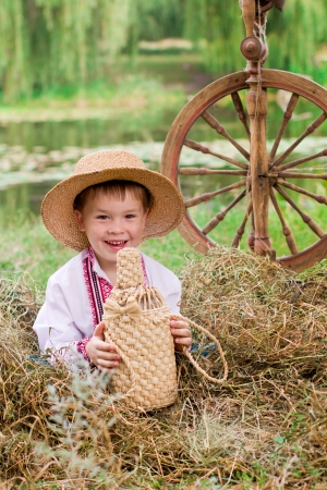 Cute child in traditional eastern european clothes with spinning-wheel outdoor photo