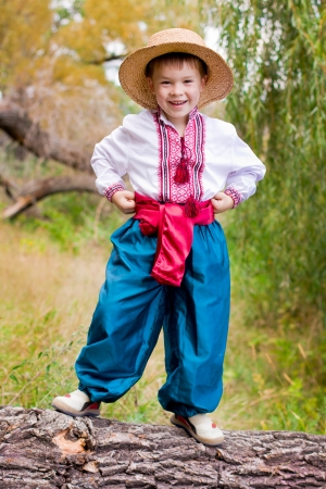 Cute child in traditional eastern european clothes outdoor photo