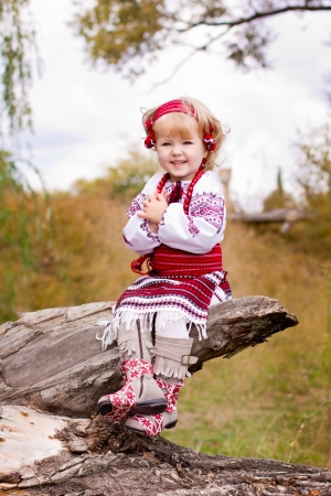 log basket: Beautiful girl in ukrainian costume sitting on a log outdoor
