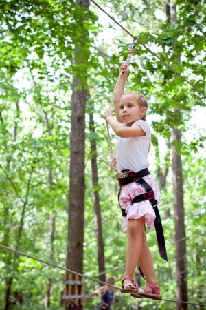 Mladá dívka balancování na laně v dobrodružství lezení vysoké drátů parku Reklamní fotografie - 14779788