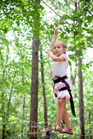 equilibrium: Young girl balancing on rope in adventure climbing high wire park