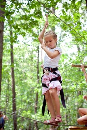 Mladá dívka balancuje na laně v dobrodružství, horolezectví vysoké drátu parku