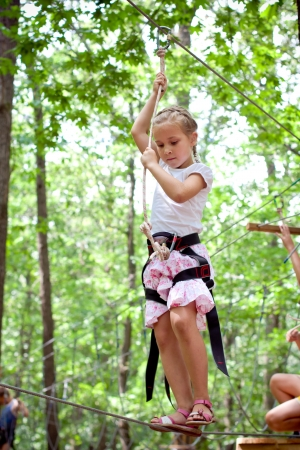 Young girl balancing on rope in adventure climbing high wire park photo