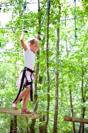Mladá dívka balancuje na laně v dobrodružství lezení vysoké drátů parku