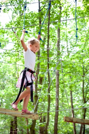 Young girl balancing on rope in adventure climbing high wire park Reklamní fotografie - 14779789