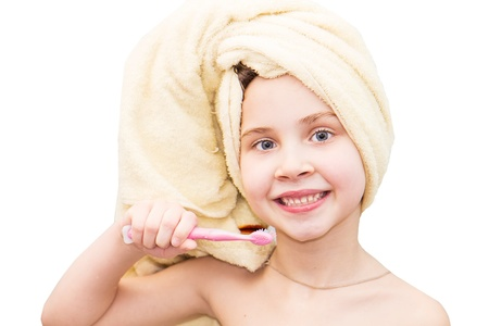 Little girl washing teeth after bath - personal hygiene education isolated on white photo