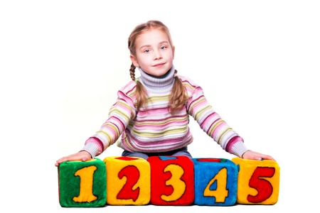 Happy girl holding blocks with numbers over white background photo