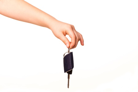 Child hand holding a car key isolated on white  New car concept photo