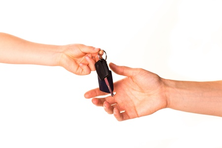 Male hand holding a car key and handing it over to another person isolated photo