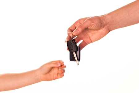 Male hand holding a car key and handing it over to another person isolated Stock Photo - 17499151