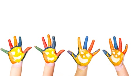 Kids hands in colorful paint with smiles raised up in the air isolated on white photo