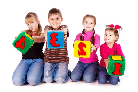 Happy kids holding blocks with numbers over white background photo