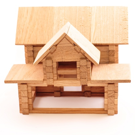 Toy wooden house isolated on white background  Building, construction concept  photo
