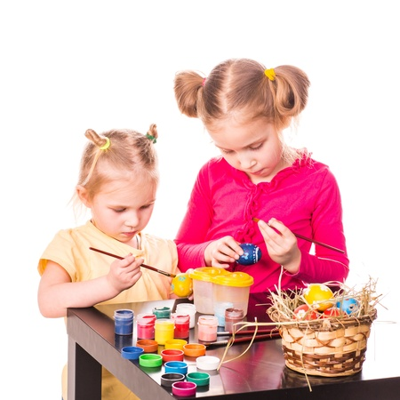 Two happy kids painting easter eggs isolated on white  Happy Easter photo