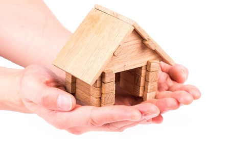 Wooden model house in hands isolated on white photo