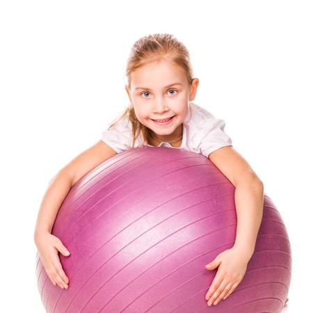 Chica juguetona en un salto de pelota en forma aislada en blanco