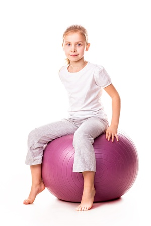 Sportive girl on a fit ball jumping isolated on white photo