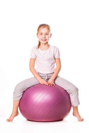 exhilarated: Sportive girl on a fit ball jumping isolated on white Stock Photo