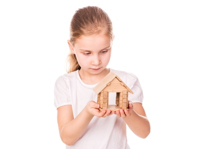 Beautiful little girl holding a toy model house isolated on white   Buying a house concept  photo