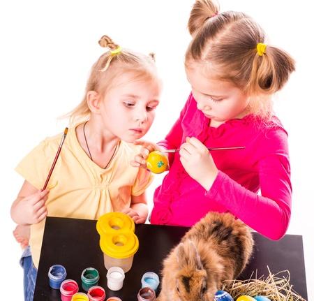 Dvě šťastné děti malovat velikonoční vejce izolovaných na bílém. Šťastné Velikonoce
